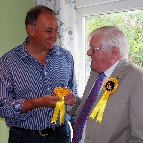 Cllr Ron Tindall (right) handing over a candidate rosette to Adrian England (left)